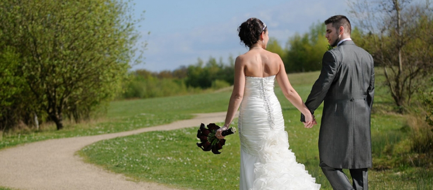 A newly married couple walk through the Millennium Country Park